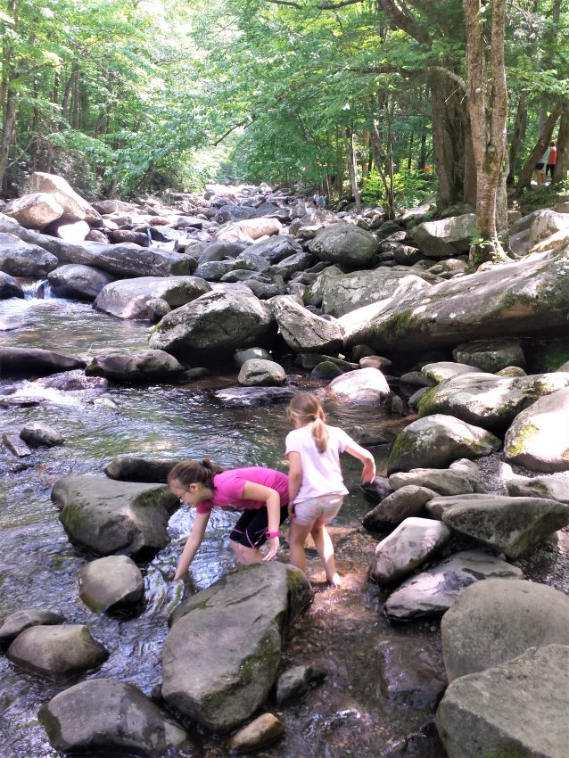 Kristi Valentinis daughters playing in the rocky river at Chimney Picnic Area 10 Things to Do With Kids in the Great Smoky Mountains